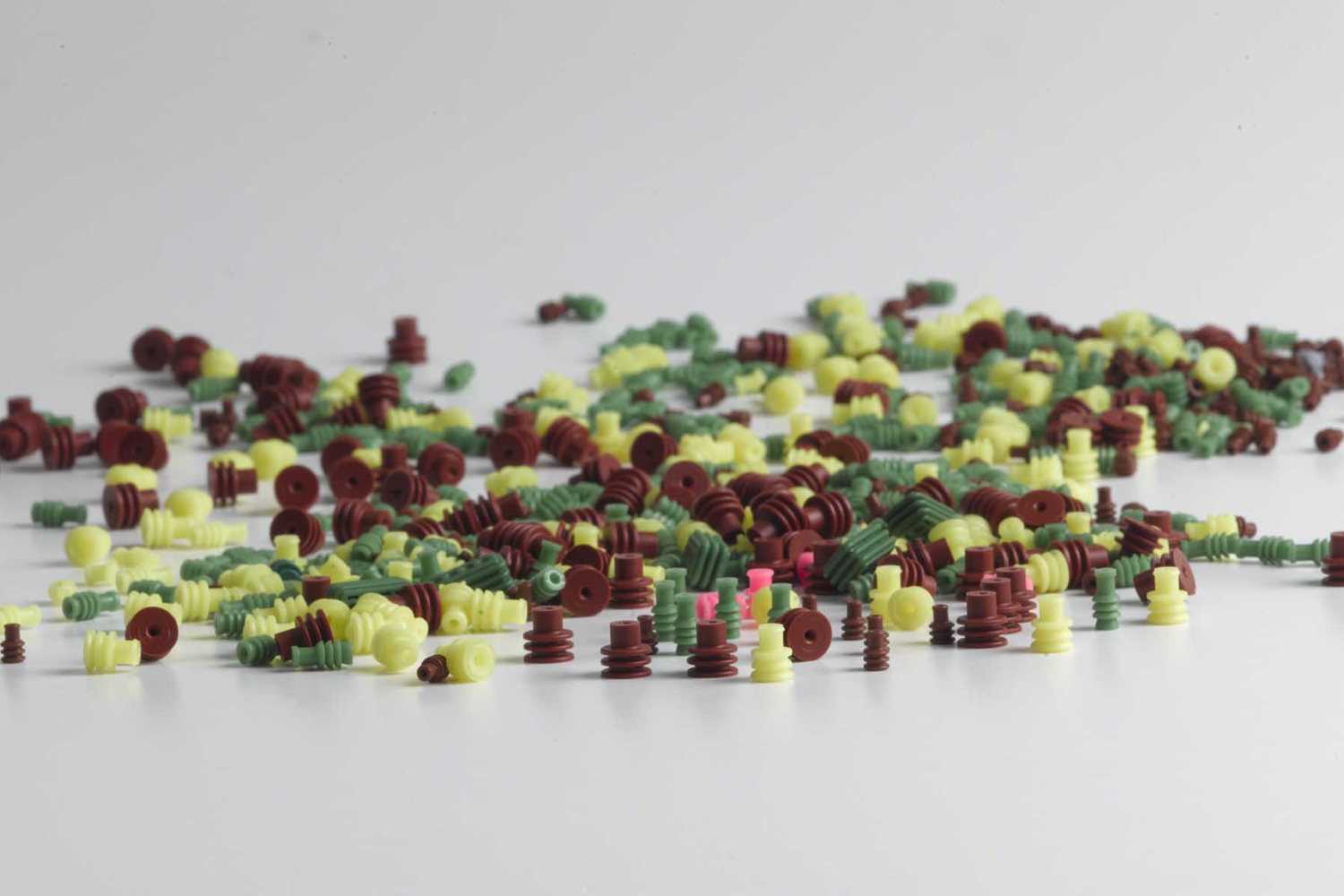 Colored rubber parts in green, red, and yellow on a table for inspection