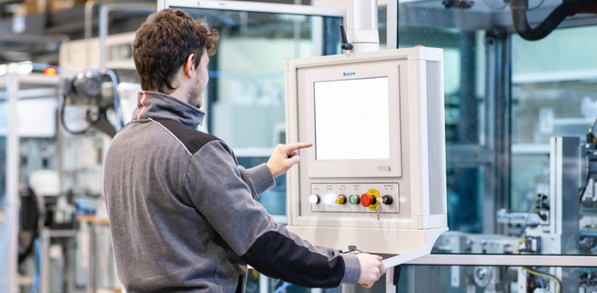 Close-up of Man pointing at a control panel of a visual inspection machine