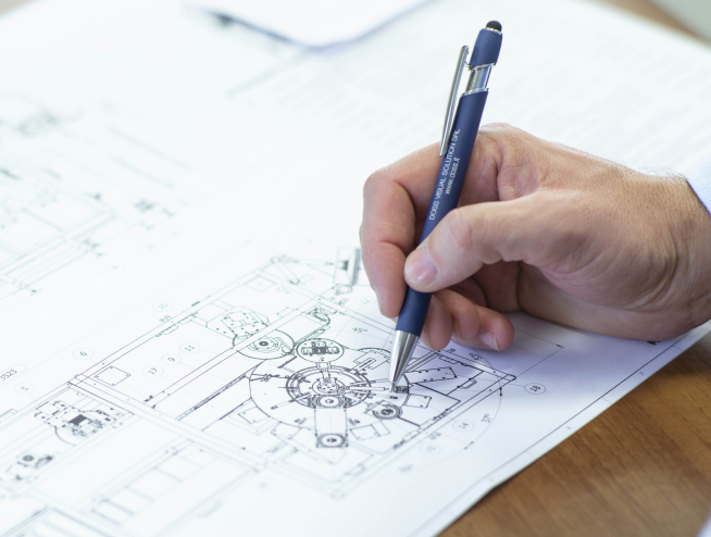 Man's hand holding a pen going over an architectural drawing with paper and table