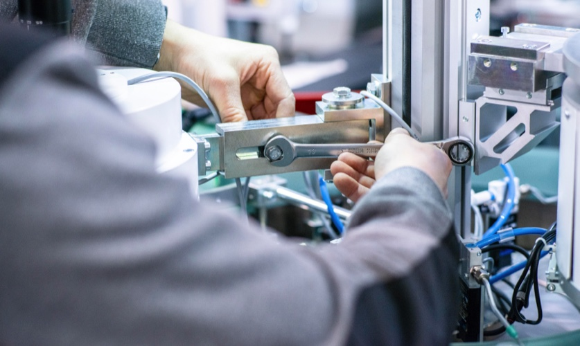 Man fixing a machine with a wrench and a bolt